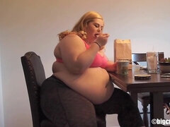 Blonde plumper rubs her belly while eating ice cream