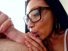 A Latina that has glasses is giving a blow job to her guy