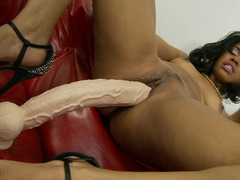 A black dame is penetrating her glabrous cunt by a big dildo