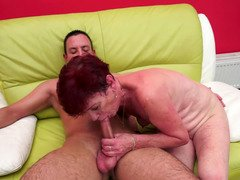 A granny with short red hair is getting penetrated in her shaved snatch