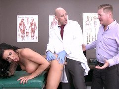 A doctor examines a hot lady in front of her husband here