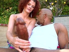 Curly dame with red hair is handling a large black love pole with her hands