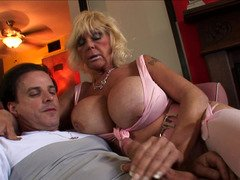 A granny that has sizeable saggy tits is getting cum over her body