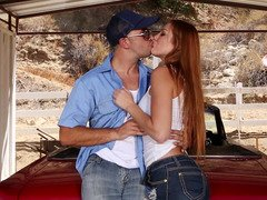 A redhead is on top of a car, getting her snatch ravaged deeply