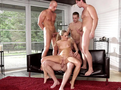 A hot blonde is getting fucked hard in a gang-fuck on the sofa