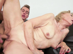 A blonde granny is placing her mouth on a immature dude's penis to kiss it