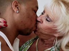 A blonde granny is receiving a sizeable black pecker on the bed