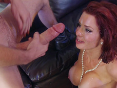 A redhead with a pretty red dress is getting a cock in her face