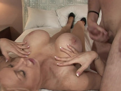 A blonde with large titties is getting fucked on the bed by a horny dude