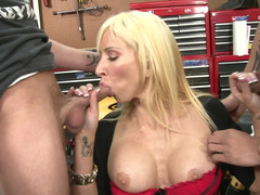 A blonde places her mouth on a couple of dicks in a garage in a threesome