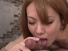 A redhead Japanese girl with a sexy face is sitting down on a dick