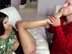 A slender girl gets her feet licked by her lover on the sofa