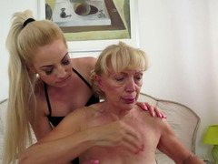A granny is getting a small dildo into her pussy in the lesbian scene
