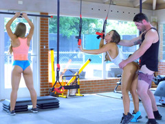 Two attractive sportswomen perform threesome in the gym
