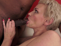 A black man is penetrating a short haired granny on the bed