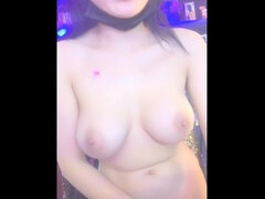 Asian babe performs a tits show in the street