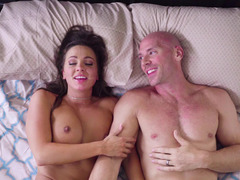 A chick and a dude roll around on the bed with one another